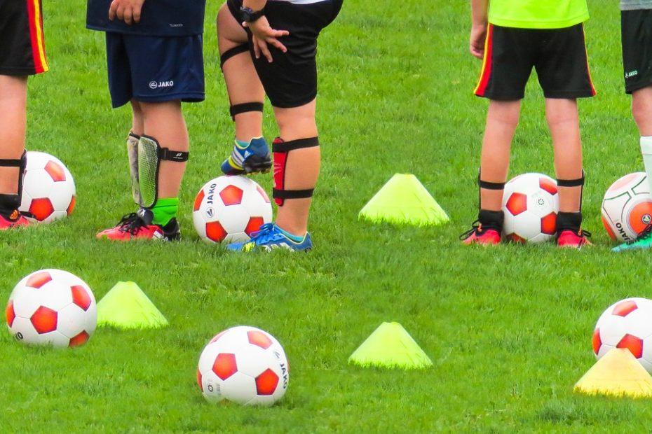 Bild: Fußballtraining einer Kindermannschaft; es liegen Bälle und Hütchen auf dem Rasen. Man sieht nur die Beine.